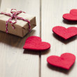 Valentine's day. A paper parcel wrapped tied with a tag. Some red hearts. A gift box wrapped with paper kraft and tied with red & white baker's twine on a brown wooden table. Vintage. — Stock Photo #64277223