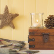 Christmas scene: a star, a blanket, a candle and two pinecones on a chest all on a white wooden table with a yellow wainscot. Vintage Style. — Stock Photo #64272923