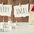 """Christmas cozy scene: some candles, a gift and a Teddy bear with Santa Claus dress on a white wooden table. """"Merry xmas"""" is hanging on a rope with clothespins. Vintage Style. — Stock Photo #64274759"""