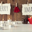 "Christmas cozy scene: candles, two pinecones and a red bowl with some shortbread on a white wooden table. ""Merry xmas"" and a red felt tree is hanging on a rope with clothespins. Vintage Style. — Stock Photo #64274885"