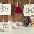 "Christmas cozy scene: candles, two pinecones and a glass bell jar with some shortbread on a white wooden table. ""Merry xmas"" and a red felt tree is hanging on a rope with clothespins. Vintage Style. — Stock Photo #64275023"