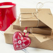 A milk mug for Santa, a red heart and some  christmas gift boxes wrapped with paper kraft and tied with red & white baker's twine on a white wooden table. Vintage Style. — Stock Photo #64275469