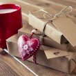 Some paper parcels wrapped tied with tags. A milk mug for Santa, a red heart and some  christmas gift boxes tied with red & white baker's twine on a wooden table. Vintage Style. — Foto Stock #64275653