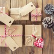 Some paper parcels wrapped tied with tags. A red heart and some christmas gift boxes wrapped with paper kraft and tied with red & white baker's twine on a wooden table. Vintage Style. — Stock Photo #64275715