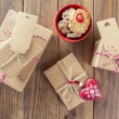 Some paper parcels wrapped tied with tags. A bowl with cookies, a red heart and some christmas gift boxes tied with red & white baker's twine on a wooden table. Vintage Style. — Stock Photo #64275873