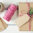A paper parcel with a pine branch, wrapped tied with a tag. Christmas gift boxe wrapped with paper kraft and tied with red & white baker's twine on a white wooden table. Vintage Style. — Stock Photo #64277007