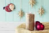 A candle and two red christmas balls. On the background Santa Claus flies between gold stars on a turquoise wooden wainscot. Christmas vintage style. — ストック写真