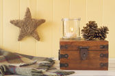 Christmas scene: a star, a blanket, a candle and two pinecones on a chest all on a white wooden table with a yellow wainscot. Vintage Style. — Zdjęcie stockowe