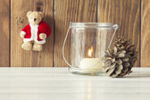 Christmas cozy scene: a candle, some pinecones and a Teddy bear with Santa Claus dress. All on a white wooden table. Vintage Style. — Fotografia Stock