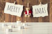 "Christmas cozy scene: some candles on a white wooden table. ""Merry xmas"" and a Teddy bear with Santa Claus dress is hanging on a rope with clothespins. Vintage Style. — Stock Photo"