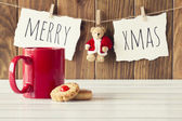 "Christmas cozy scene: a red mug and some shortbread on a white wooden table. ""Merry xmas"" and a Teddy bear with Santa Claus dress is hanging on a rope with clothespins. Vintage Style. — Stock Photo"