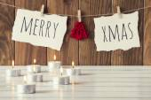 """Christmas cozy scene: some candles on a white wooden table. """"Merry xmas"""" and a felt tree is hanging on a rope with clothespins. Vintage Style. — Stock Photo"""