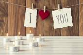 """I love you"" is hanging on a rope with clothespins. Some candles on a white wooden table. A brown wainscot as background. Vintage Style. — Stock Photo"