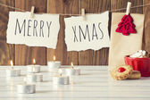 "Christmas cozy scene: some candles, a gift and a red bowl with shortbreads on a white wooden table. ""Merry xmas"" is hanging on a rope with clothespins. Vintage Style. — Stock Photo"