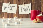 "Christmas cozy scene: candles, a red mug and a bowl with some shortbread on a white wooden table. ""Merry xmas"" is hanging on a rope with clothespins. Vintage Style. — Stock Photo"