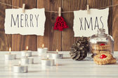 "Christmas cozy scene: candles, two pinecones and a glass bell jar with some shortbread on a white wooden table. ""Merry xmas"" and a red felt tree is hanging on a rope with clothespins. Vintage Style. — Stock Photo"