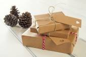 Some paper parcels wrapped tied with tags. Christmas gift boxes wrapped with paper kraft and tied with red & white baker's twine on a white wooden table. Vintage Style. — Stock Photo