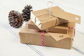 Некоторые бумажные пакеты обернули сыгранный вничью признаки. рождественские подарочные коробки, обернутые с бумажной крафт-бумагой и, сыграли вничью с бечевкой красного & белого пекаря на белом деревянном столе. старинный стиль. — Стоковое фото