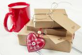 A milk mug for Santa, a red heart and some  christmas gift boxes wrapped with paper kraft and tied with red & white baker's twine on a white wooden table. Vintage Style. — Stock Photo