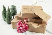 Some paper parcels wrapped tied with tags. A red heart and some  christmas gift boxes wrapped with paper kraft and tied with red & white baker's twine on a white wooden table. Vintage Style. — Stock Photo
