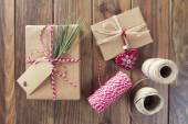 Some paper parcels wrapped tied with tags. A red heart and some christmas gift boxes wrapped with paper kraft and tied with red & white baker's twine on a wooden table. Vintage Style. — Stock Photo