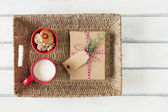 A paper parcel wrapped tied with a tag, a red bowl with shortbreads and a milk mug. A christmas gift box wrapped with paper kraft and tied with red & white baker's twine. Vintage Style. — Stock Photo
