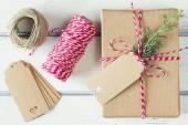 Une parcelle de papier avec une branche de pin, enveloppée à égalité avec une balise. Boxe de cadeau de Noël enveloppé de papier kraft et lié avec de la ficelle de baker rouge & blanc sur une table en bois blanche. Style Vintage. — Photo