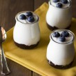 Three jars with greek yogurt, blueberries and jam — Stock Photo #64282081