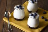 Three jars with greek yogurt, blueberries and jam — Fotografia Stock
