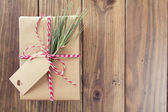 A paper parcel wrapped tied with a tag. A christmas gift box wrapped with paper kraft and tied with red & white baker's twine on a wooden table. Vintage Style. — Stock Photo