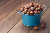 Hazelnuts in a blue bucket on a wooden table. Vintage Style. — Stockfoto