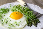 Breakfast of fried eggs, asparagus and watercress salad — Stock Photo