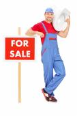Plumber standing by for sale sign — Stock Photo