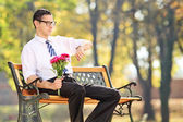 Man holding flowers on bench — Stockfoto