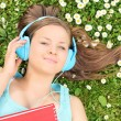 Girl in meadow listening to music — Stock Photo #52648765