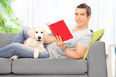 Man reading book with dog — Stock Photo