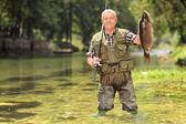 Proud fisherman holding fish — Foto de Stock