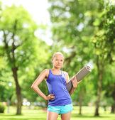 Female athlete holding exercising mat — Photo