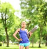 Female athlete holding exercising mat — Stok fotoğraf