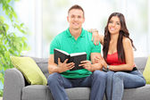 Couple reading book at home — Stock Photo