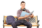 Student with headphones reading book — Stock Photo