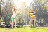 Mature couple exercising with hula hoops — Stock Photo
