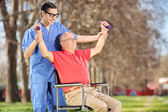 Physiotherapist exercising with patient in park — Stockfoto