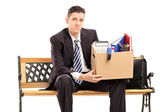 Fired businessman holding box with stuff — Stock Photo