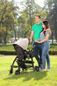 Parents pushing baby stroller in park — Stock Photo