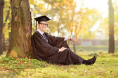 College graduate sitting in park — Foto de Stock