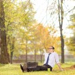 Businessman relaxing seated on the grass in park — Stock Photo #57523759