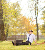 Businessman relaxing seated on the grass in park — Stock Photo
