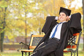 Graduate student sitting on bench — Foto de Stock