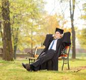 Graduate student on bench in park — Foto de Stock